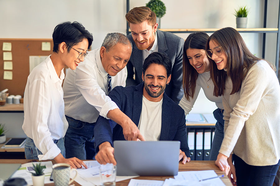 Employee Benefits - Group of Employees Helping Their Colleague on Laptop in the Office