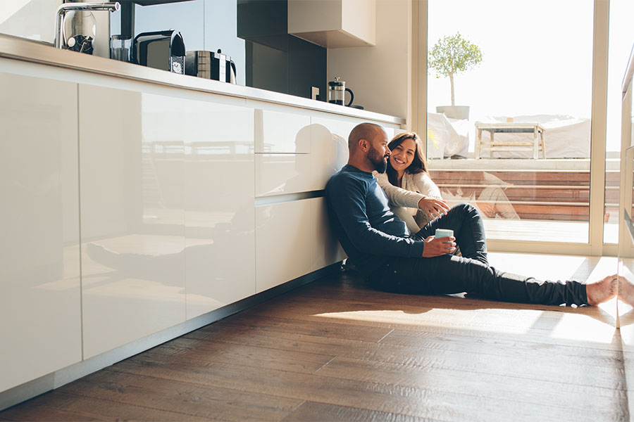 Insurance Quote - Young Couple Sitting on Floor in Their Kitchen